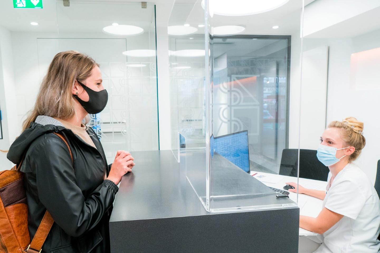 Der Empfangsbereich der Zahnklinik Mühldorf am Inn mit den getrennten Terminals ist mit Trennband, Hinweisschild, Desinfektionsspender sowie Schutzscheiben optimal an die Situation angepasst. Foto: Zahnklinik Mühldorf am Inn GmbH